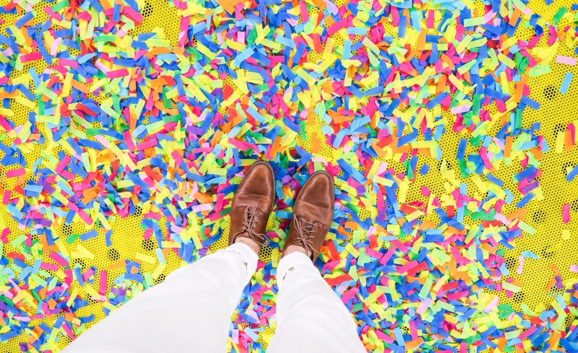 An introvert stands on confetti from a party.