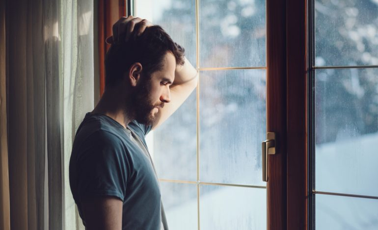 An introvert stands in front of a window, looking sad.