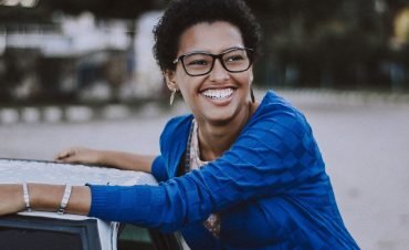 An INFJ personality smiles by a car.