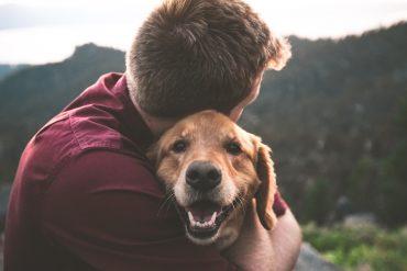 An introvert hugs his pet.