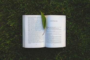 a book in the grass that represents Michelle Obama's Becoming memoir
