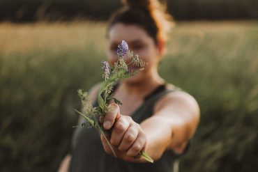 an INFJ holds a flower up to the camera