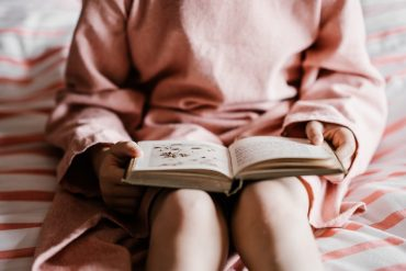 an introverted girl reads a fiction book