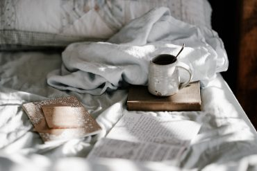 coffee, a book, and a notebook on a bed, representing how introverts can slow down and enjoy life more