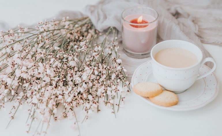 a candle, cookies, coffee, and flowers, representing an introvert's hygge all year round