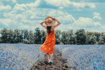 An introvert stands in a field of flowers